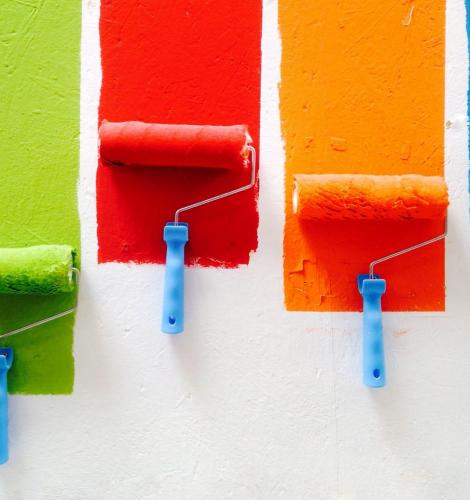 Green, red, orange, and blue paint rollers