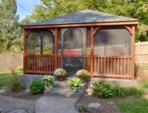 Brown wood rectangle gazebo in residential backyard