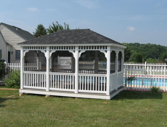 White rectangle wooden gazebo in residential backyard